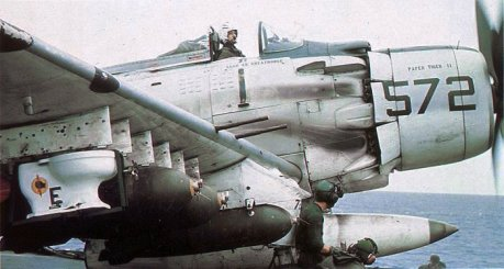"""A-1H of VA-25 """"Fist of the Fleet"""" prepares to fly a mission in 1965 with a special purpose bomb, outfitted with an 'E' award for battle efficiency, aboard CV-41 """"Magic"""" Midway.  This bomb was actually flown and dropped on a mission as a joke. The North Vietnamese actually accused the US of """"bacteriological"""" warfare because of the stunt."""